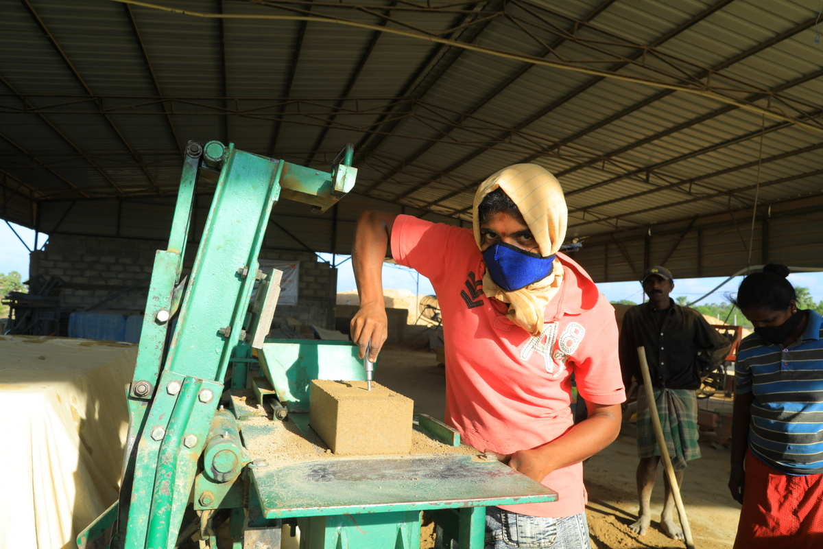 A worker operating the press to produce compressed stabilized earth blocks in Batticaloa yard